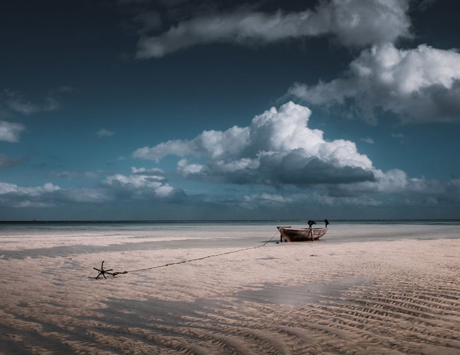 The high tides of Zanzibar create some fantastic images as boats get stranded on the sand. Anchored Beauty In Nature Cloud - Sky Clouds Fishing Boat Horizon Over Water Land Mode Of Transportation Nature Nautical Vessel Outdoors Sand Scenics - Nature Sea Sky Tranquility Water
