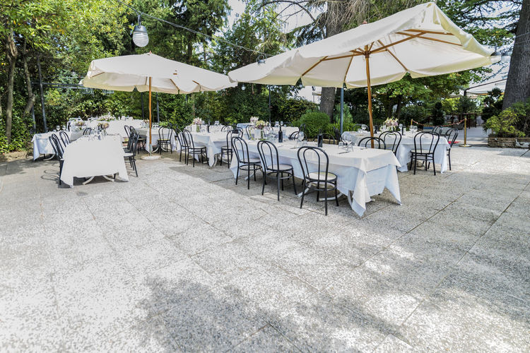 Outdoor restaurant tables ready for wedding party Chair Seat Protection Umbrella Parasol Table Absence Day Nature Security No People Land White Color Shade Sunshade In A Row Plant Arrangement Tree Outdoors Setting