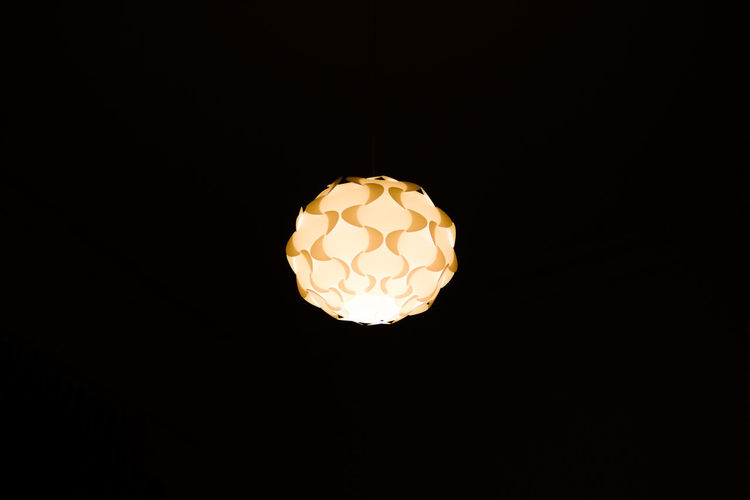 Nice hanging round shaped decorative chandelier on a very dark room. Sun resemblance. Dark Hanging Isolated Light Modern Retro Art Background Brightly Lit Cealing Chndelier Concept Decoration Design House Interior Interior Design Irradiated Lamp Luster Luxury Round Ship Sun Warm