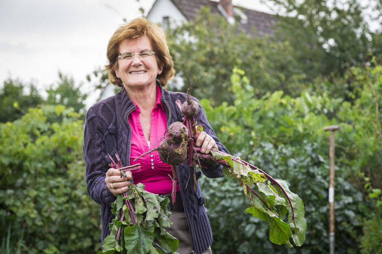 Portrait Of Smiling Woman Holding Root Vegetable Against Plants