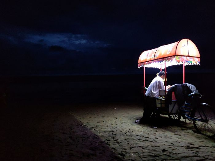 Vendor with concession stand standing at beach during night