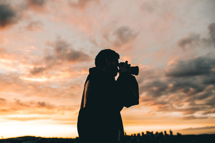 Rear view of silhouette woman photographing against sky during sunset