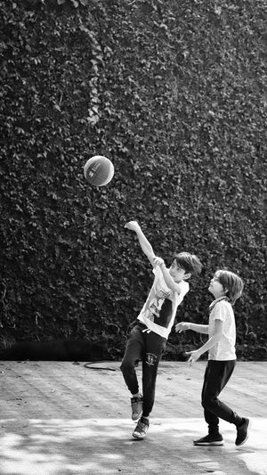 Siblings playing basketball on footpath