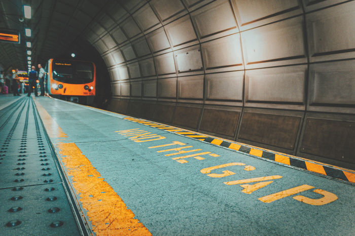 A train awaits passengers to board in a quiet tube station. To see more of my work head to http://www.timothybarkerjr.com/ Communication Information Mind The Gap Road Marking Shadow Sign Subway Transportation Transportations Tube Station  Waiting Train Yellow