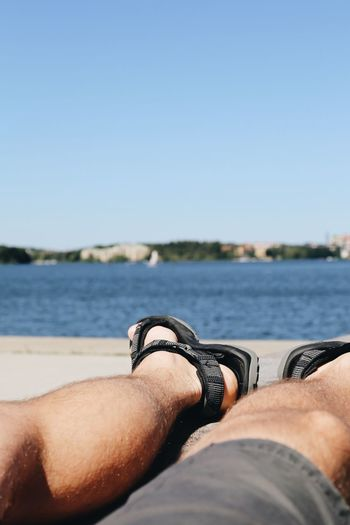 Low section of man relaxing at beach against sky