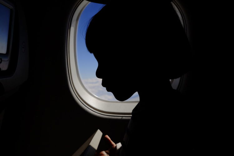 Close-up silhouette boy by airplane window