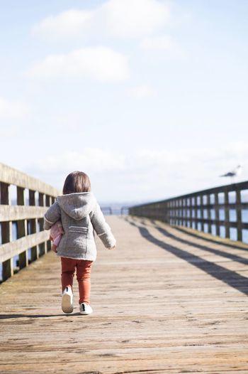 Rear View Of Girl Walking On Pier