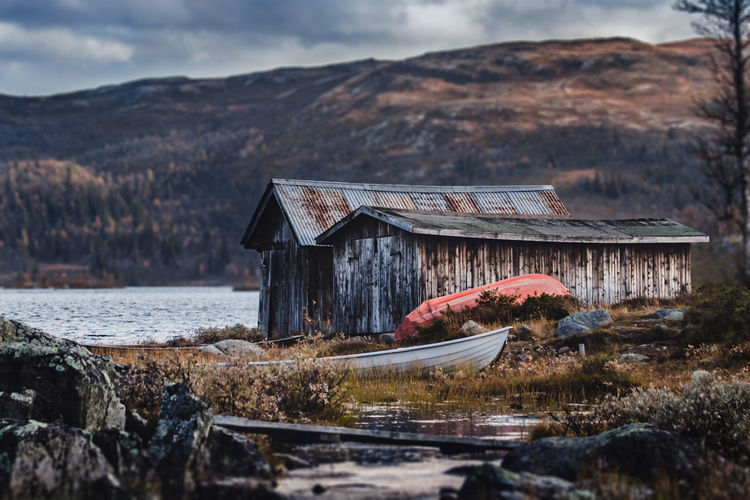 Abandoned house by lake against sky