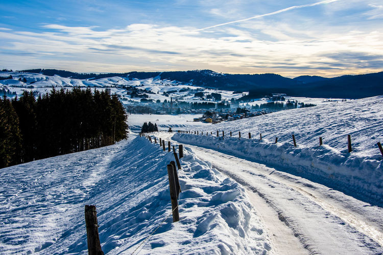 Snow between mountains and valleys with beaten path divided by barbed wire in asiago, vicenza, italy