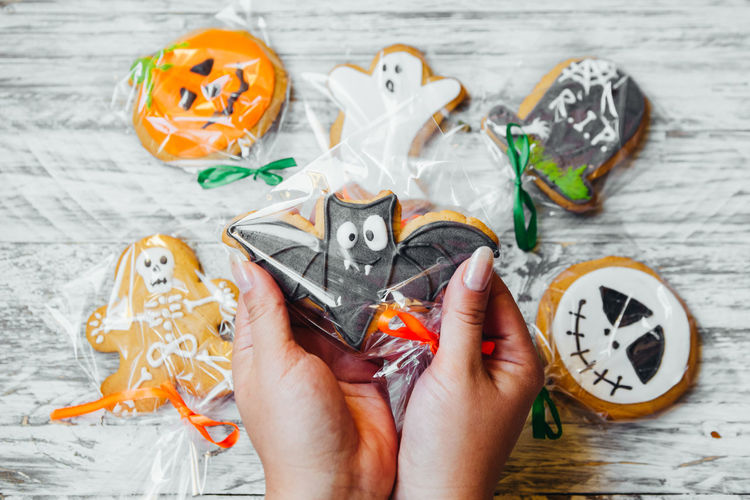 Cropped hands of woman holding various cookies wrapped in plastic over wooden table during halloween