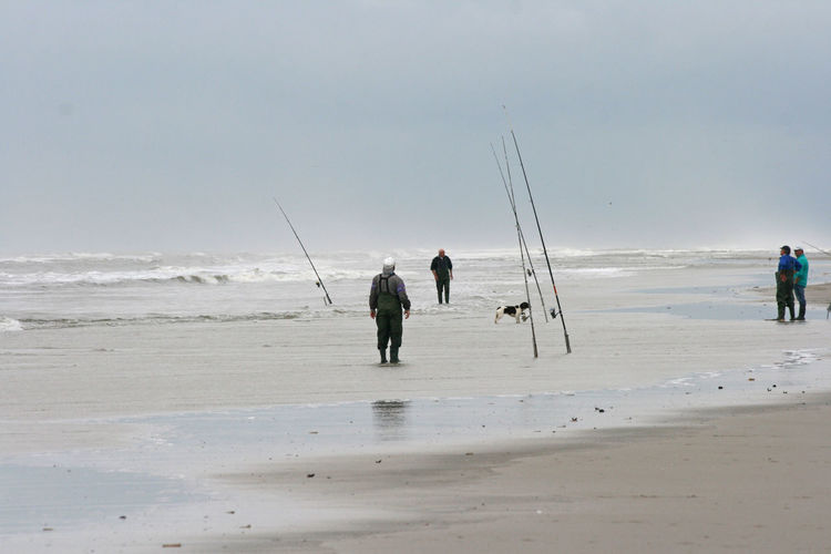 Men fishing on beach against clear sky