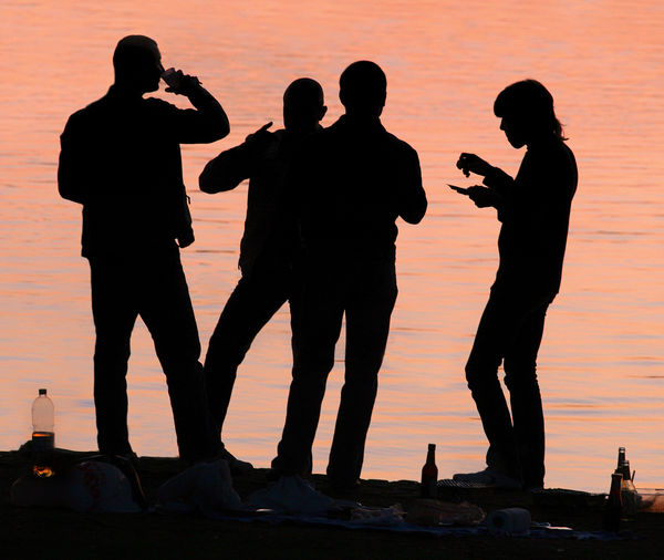 Silhouette people photographing against sky during sunset