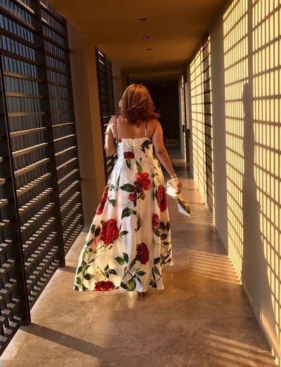 Sunlight falling on woman in dress walking through corridor