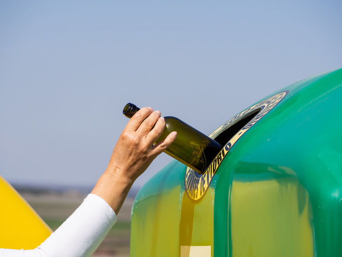 Midsection of person holding bottle against clear sky