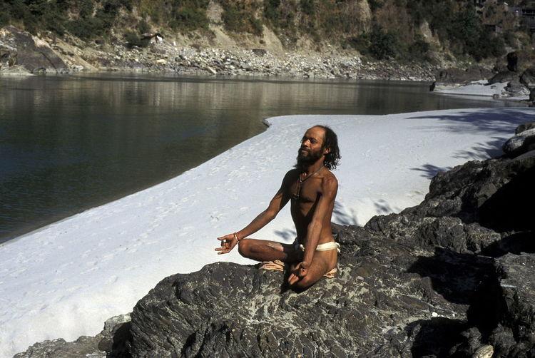 Man Meditating On Rock By Frozen Lake