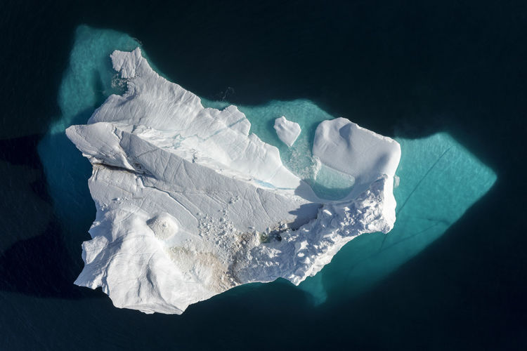 Aerial view of an iceberg in Scoresby Sund fjord, east coast of Greenland. Greenland Ice Looking Down Melting Aerial Aerial View Arctic Beauty In Nature Blue Cold Cold Temperature Frozen Glacier High Angle View Ice Iceberg Iceberg - Ice Formation Melting Ice Nature Ocean Scoresby Sound Sea Straight Down Water Winter