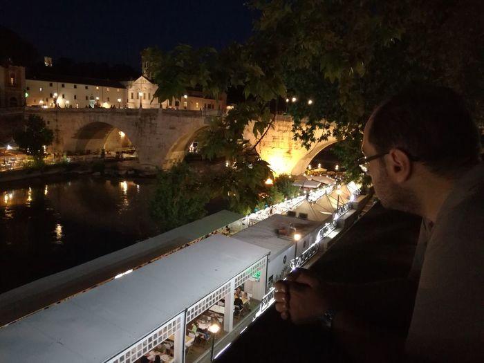 Man standing by illuminated city at night