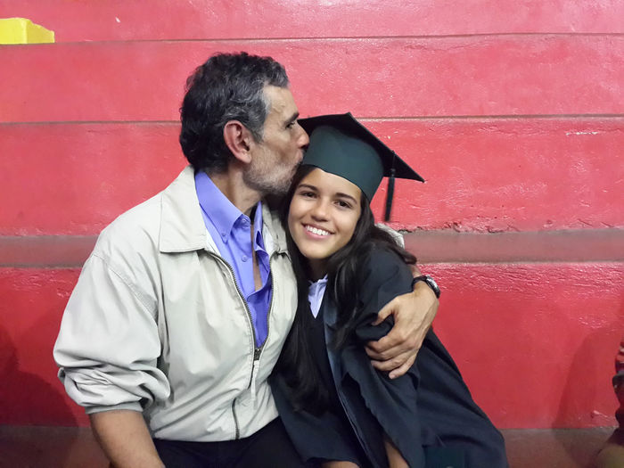 Father Kissing Graduate Daughter While Sitting Against Red Wall