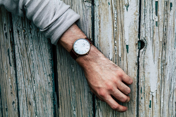 Close-up of human hand on wooden fence