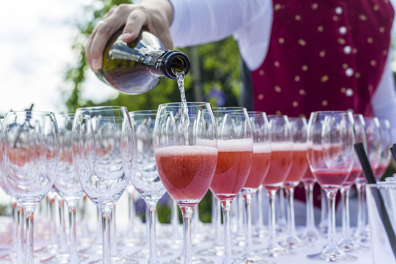 Midsection of bartender pouring aperitif in champagne flutes on table during outdoor party
