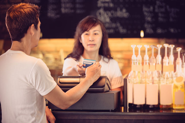 Credit card payment . Cash Cashier Machine Coffee Shop Credit Card Man Payment Register Restaurant Warm Light White Costume Women