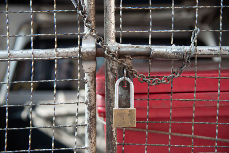 Close-up of padlock on metal fence