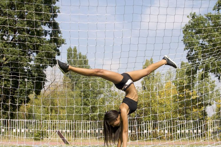Full length of woman doing handstand against net