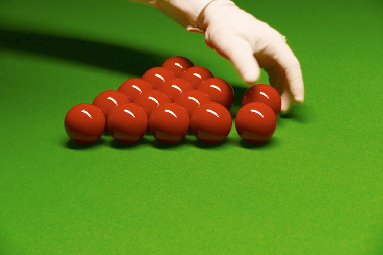 Cropped hand adjusting balls on pool table