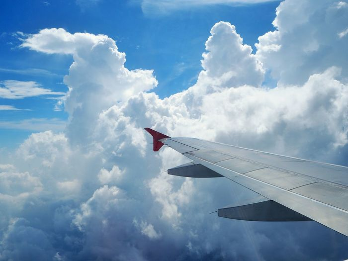 Clouds in the sky from airplane's passenger window seat view Nature Outdoor Cloud Seat Sky Airplane Flying Transportation Aircraft Wing Day Mid-air Motion Travel Aerospace Industry High Angle View Window Passenger Craft Aircraft Travel Destinations Blue White Background Sunshine View Skyview Look Out The Window Metal