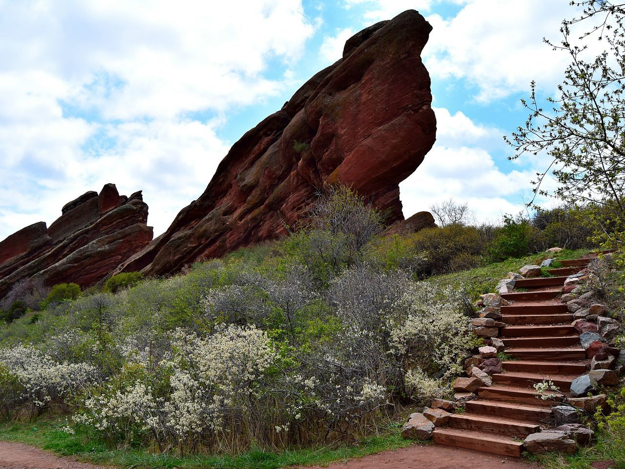 Steps And Plants By Rock Formations Against Cloudy Sky