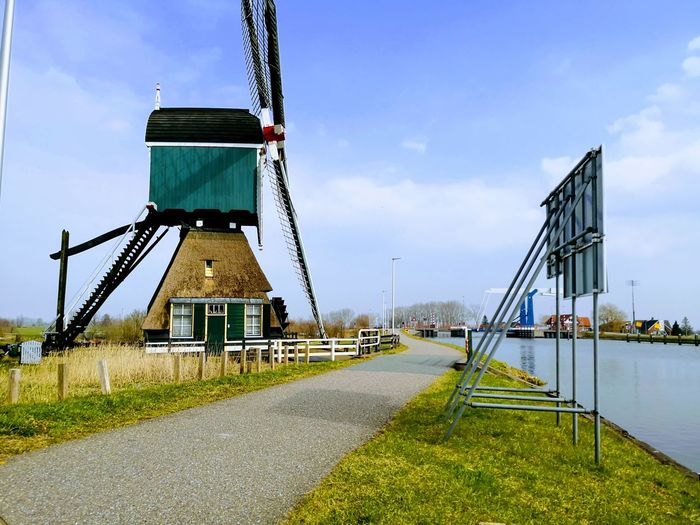 Windmill by river against sky