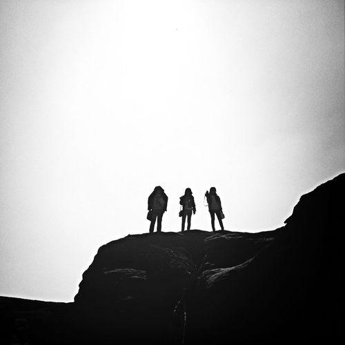 Three women standing on top of rock