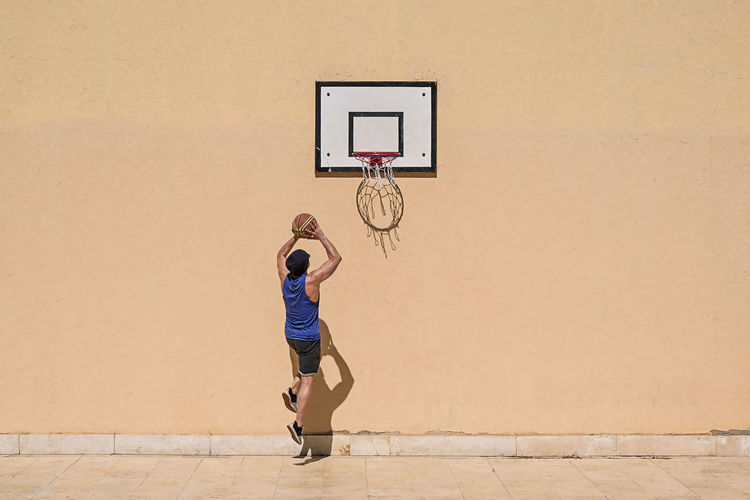Basketball - Sport Basketball Hoop One Person Full Length Sport Court Lifestyles Leisure Activity Basketball - Ball Basketball Player Wall - Building Feature Men Real People Motion Architecture Young Adult Day Skill  Ball Outdoors Shorts Jumping Copy Space Fitness 17.62° 17.62°