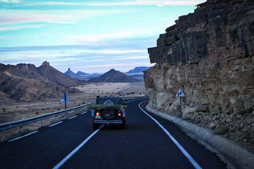 Jeep in Algerian Sahara Beauty In Nature Car Cloud - Sky Day Highway Land Vehicle Mode Of Transport Mountain Mountain Range Mountain Road Nature No People Outdoors Road Road Marking Scenics Sky The Way Forward Transportation Winding Road
