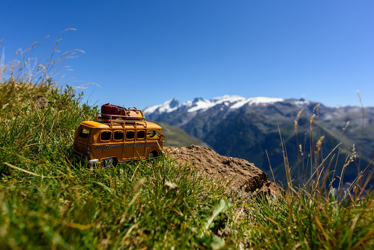 Hippie van (toy) in the grass with view on a glacier. French Alps, France, europe Exploring Green Color Holiday Mountain View Transportation Travel Traveling Travelling Trip Vacations Wanderer Wanderlust Blue Sky Bus Day Destination Glacier Hippie Lifestyles Luggage Roadtrip Summer Van Wilderness Yellow
