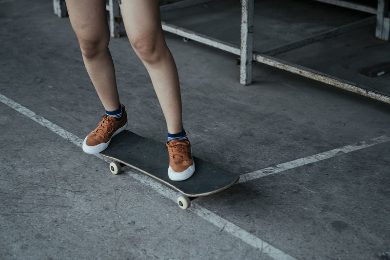 Low section of woman standing on skateboard