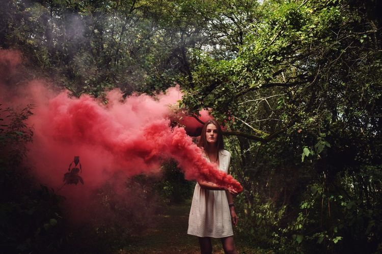 Portrait of woman holding distress flare while standing by trees
