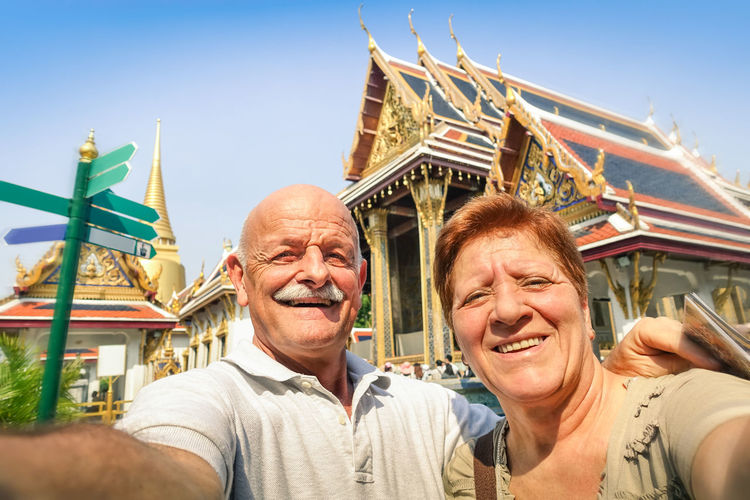 Portrait of smiling couple standing against temple