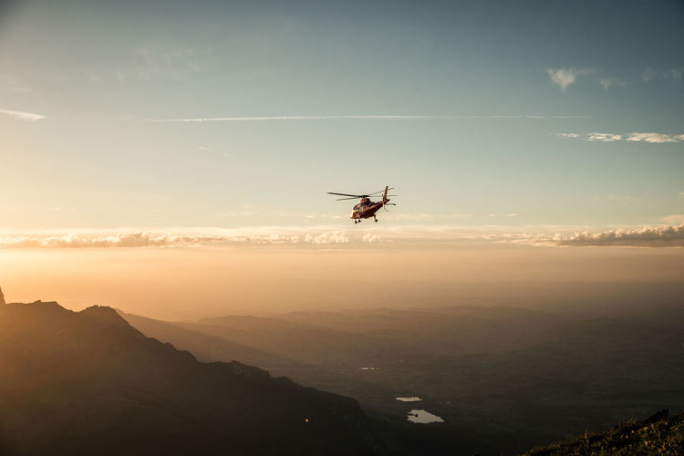 Helicopter Flying Over Mountains Against Sky During Sunset