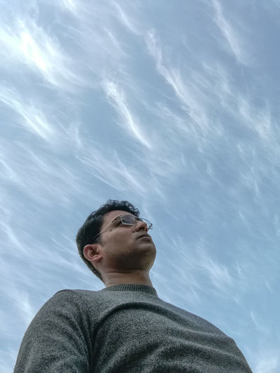Low angle view of mature man looking away while standing against sky