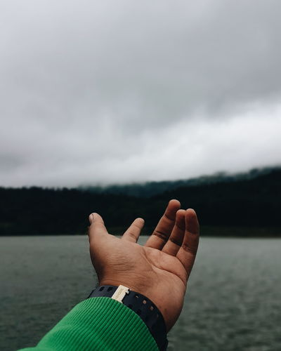 Cropped Hand Gesturing Over Lake Against Sky