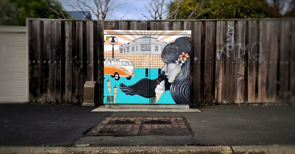 Woman standing by graffiti on footpath