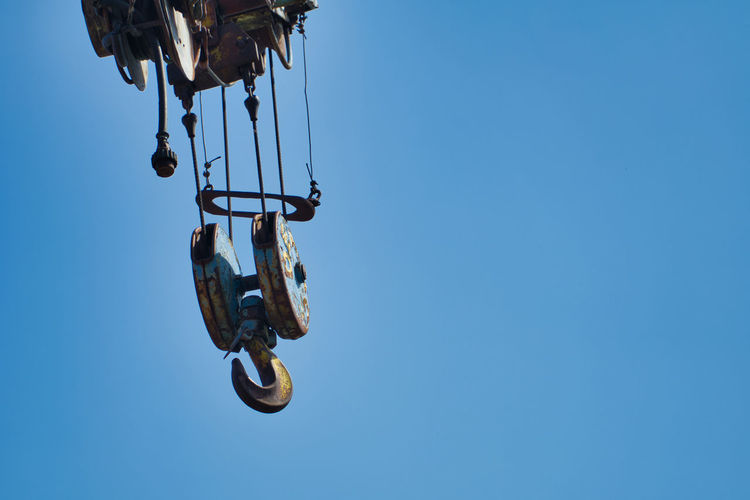 Low angle view of chain hanging against clear blue sky