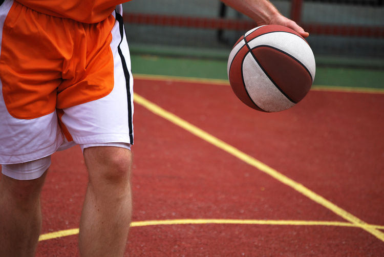 Midsection Of Man Playing Basketball On Court