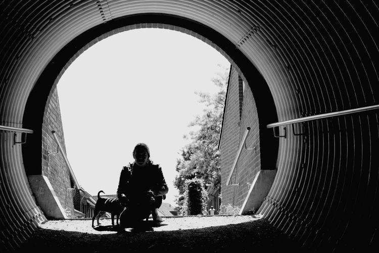 Woman with dogs crouching in tunnel