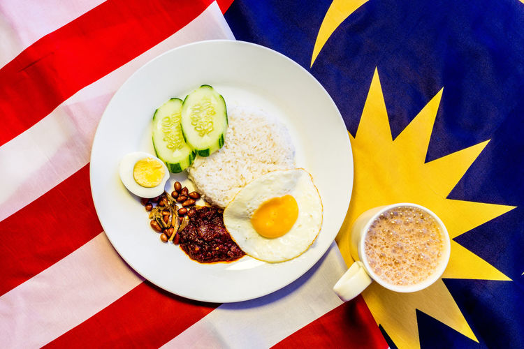 """Malaysian Breakfast - Nasi Lemak and Teh Tarik on Malaysia Flag. Both dishes are unofficially the national breakfast dish of Malaysia. Nasi Lemak literally means Fatty Rice - coconut infused riced eaten with spicy sambal, peanuts, fried anchovies, cucumber, boiled or fried egg. Teh Tarik literally means Pulled Milk Tea where Its name is derived from the pouring process of """"pulling"""" the drink during preparation. ASIA EyeEm Best Shots EyeEm Food Lovers Food And Drink Fried Egg Kuala Lumpur Nasi Lemak Patriotism Teh Tarik Carbohydrates Close-up Conceptual Flag Flat Lay Local Food Malaysia Milk Tea Ready-to-eat"""