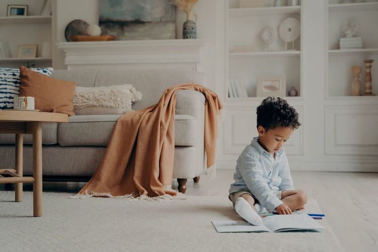 Rear view of boy looking at book at home