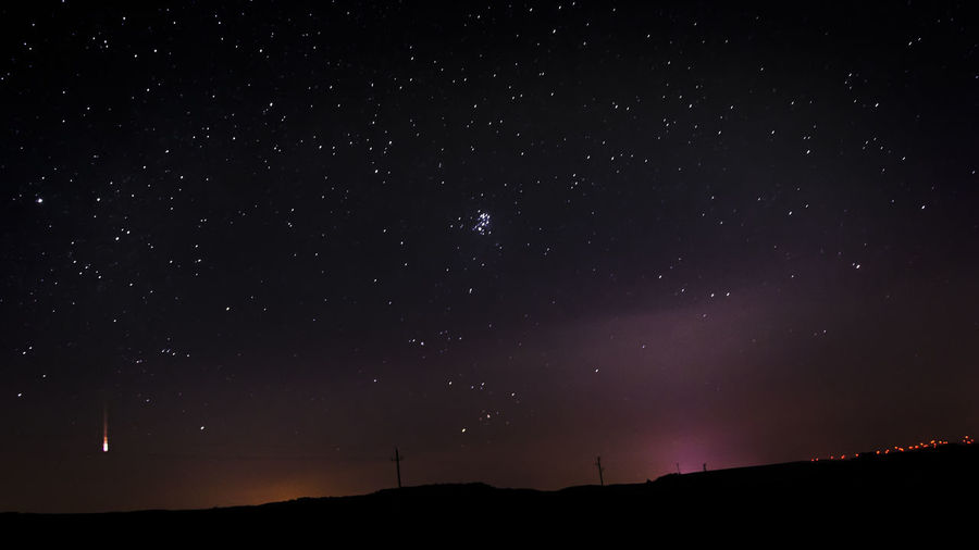 Meteor and star field over landscape at night