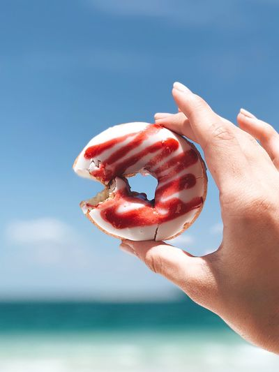 Cropped Hand Holding Donut Against Sky