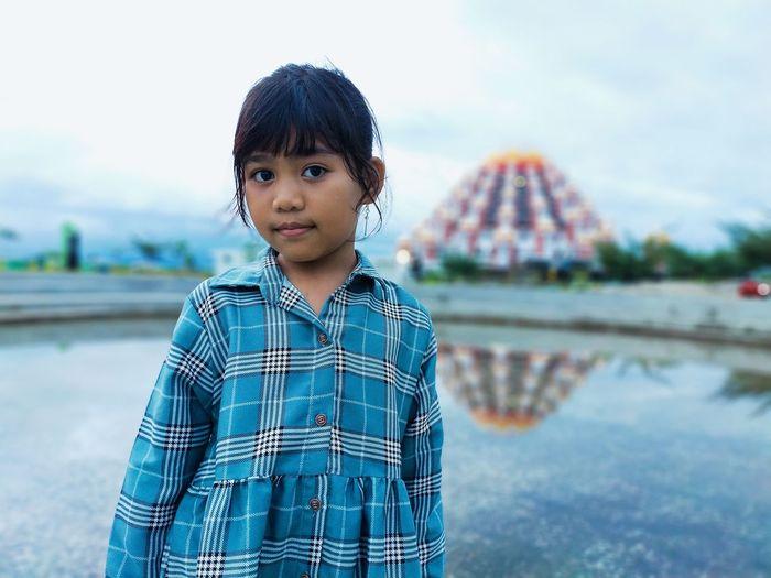 Portrait of cute girl standing in water